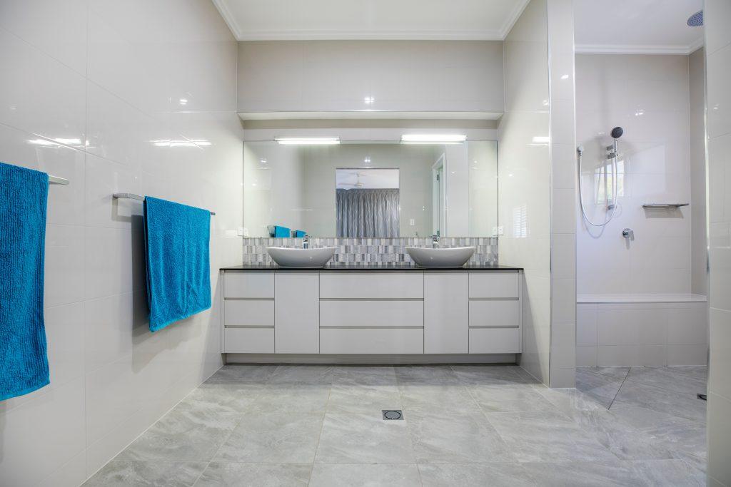 Toalhas azuis em toalheiro linear na parede de um banheiro cinza