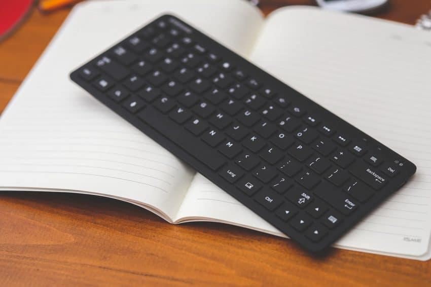Imagem mostra teclado compacto sem fio sobre páginas de caderno em branco.