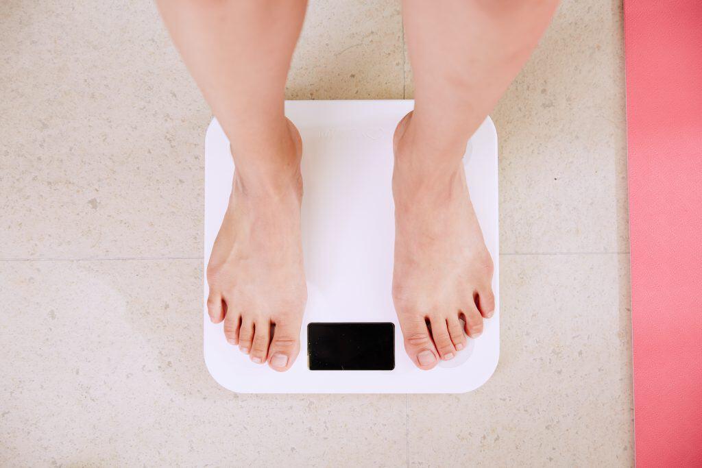 Imagem mostra os pés de uma pessoa sobre uma balança branca.