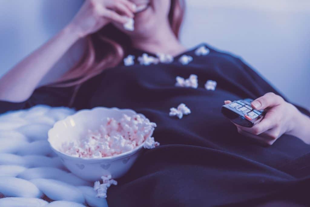 Mulher deitada, com pipocas no colo e controle remoto na mão, com pequeno prato de pipoca ao lado.