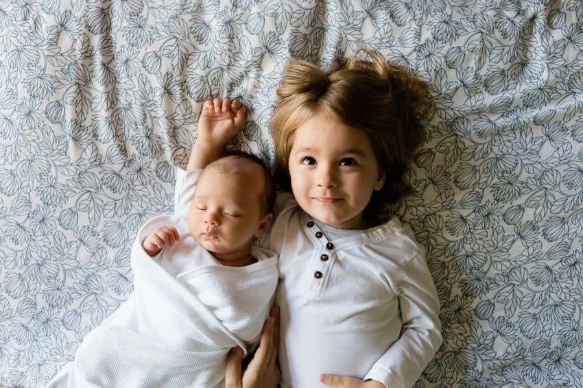Duas crianças, uma maior e um recém-nascido, vistas de cima deitadas em uma cama.