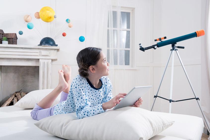 Niña en cuarto blanco con telescopio