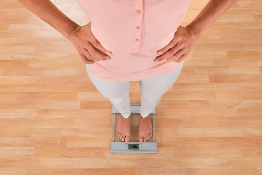 Imagem mostra uma pessoa utilizando uma calça jeans antiga para mostra como perdeu peso, além do desenho de uma balança ao lado.