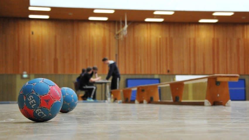 Imagem de um salão com duas bolas de handebol de tamanhos diferentes no chão.