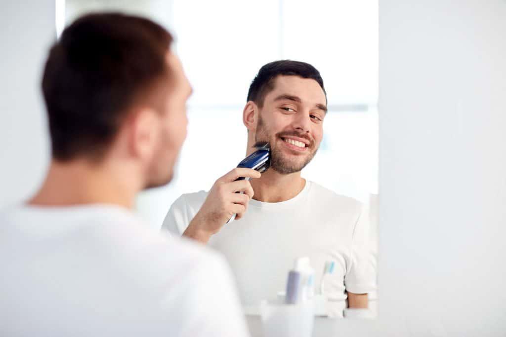 Imagem de homem fazendo a barba com barbeador elétrico Philips.
