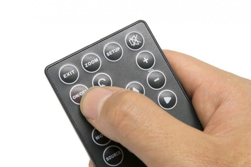 O dedo de uma mão apertando um botão de um controle remoto.