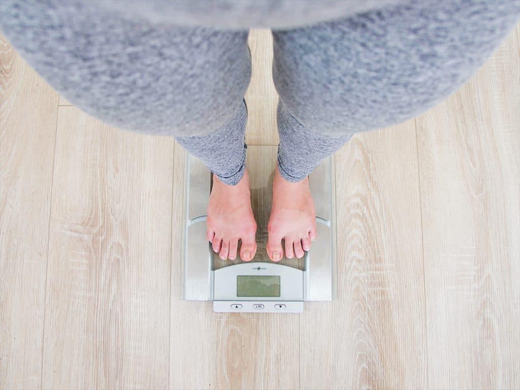 Imagem mostra os pés de uma pessoa calçando tênis em frente a uma balança digital da cor branca.