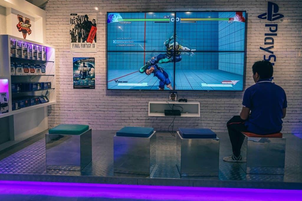 Imagem mostra um homem sentando em frente a uma grande tela de TV jogando videogame.