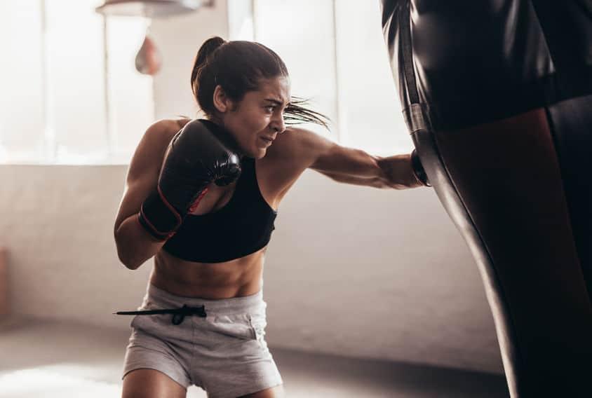 Imagem mostra uma mulher treinando com um saco de boxe.