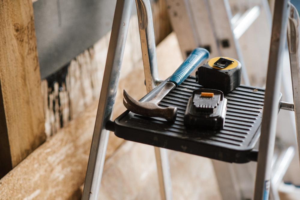 Martelo e duas fitas métricas em um degrau de escada de alumínio
