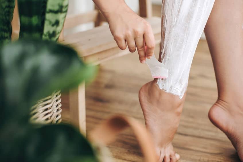 Foto mostra mulher passando uma espátula em uma das pernas coberta de creme depilatório.