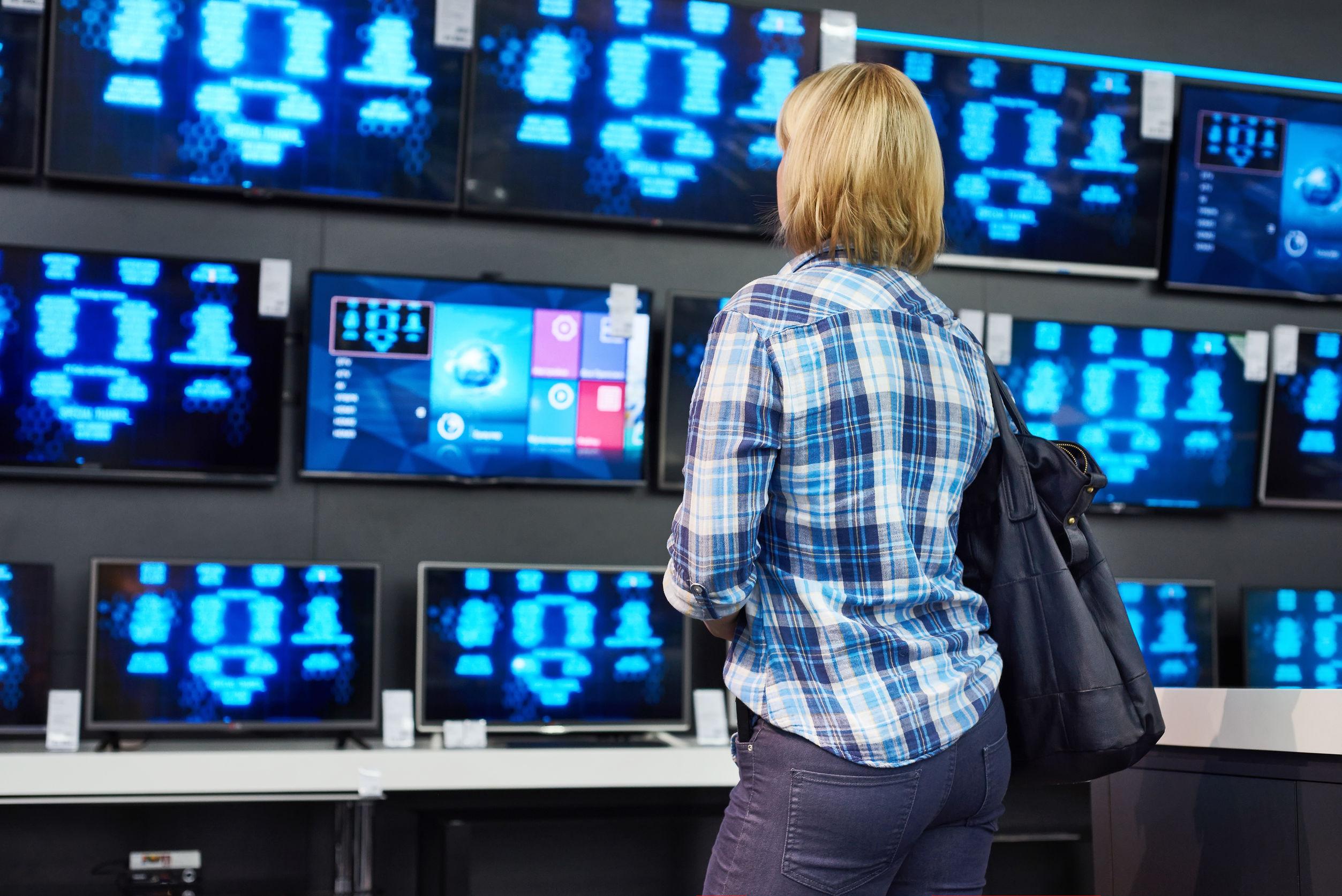 Chica rubia mira las TV LCD en supermercado