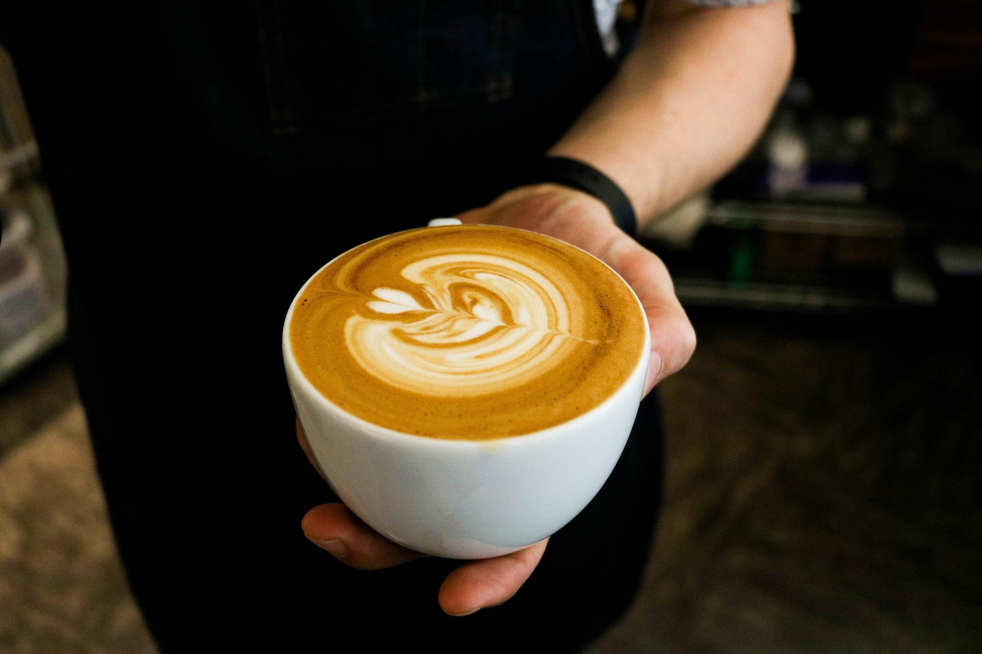 Pessoa segurando xícara de café com espuma de leite.
