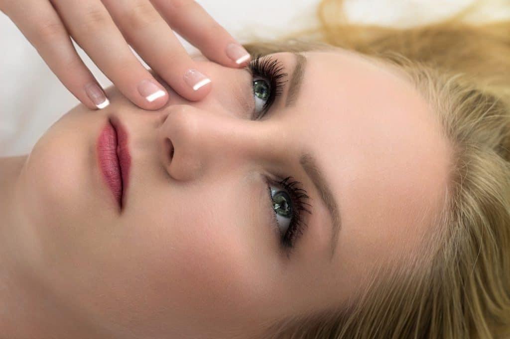 Mulher com pele saudável e a mão no rosto.