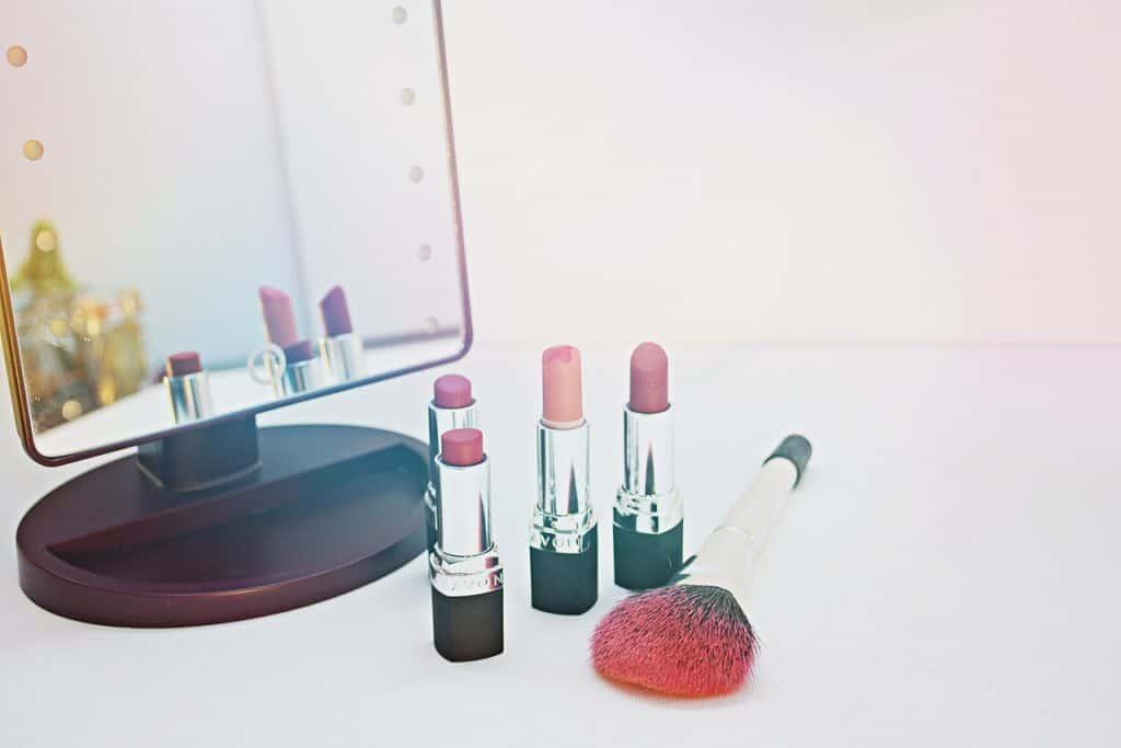 Foto de quatro batons em tonalidades de rosa, um espelho e um pincel de maquiagem, em cima de uma superfície branca.