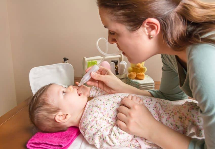 Bebê deitado e a mãe segurando uma das pontas da mangueira próximo a narina da criança enquanto suga com a boca a outra ponta da mangueira.
