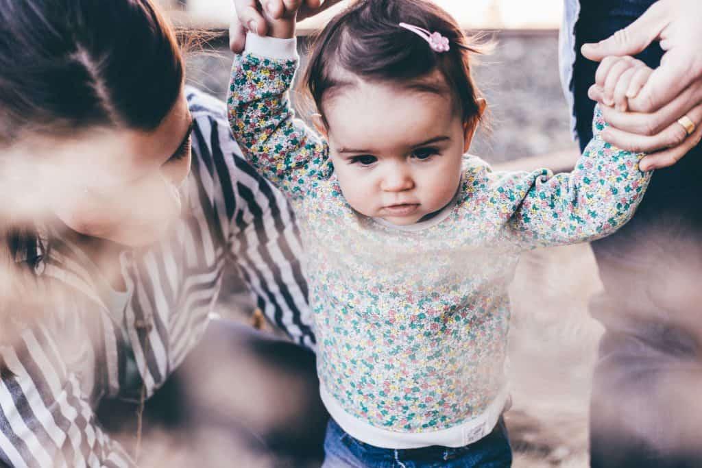 Bebê em pé com mãe ao lado.