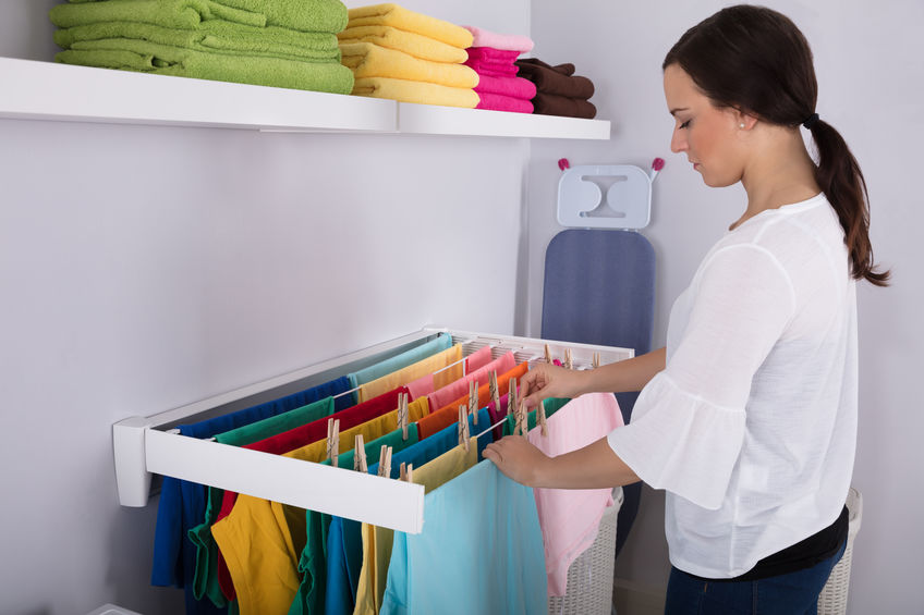 Imagem de uma mulher estendendo roupas em um varal.