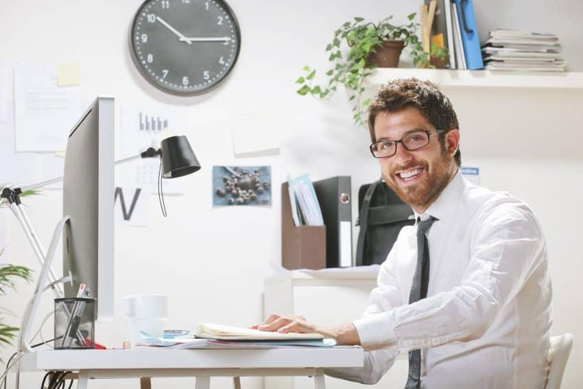 homem sorrindo trabalhando sentado em sua mesa no escritório