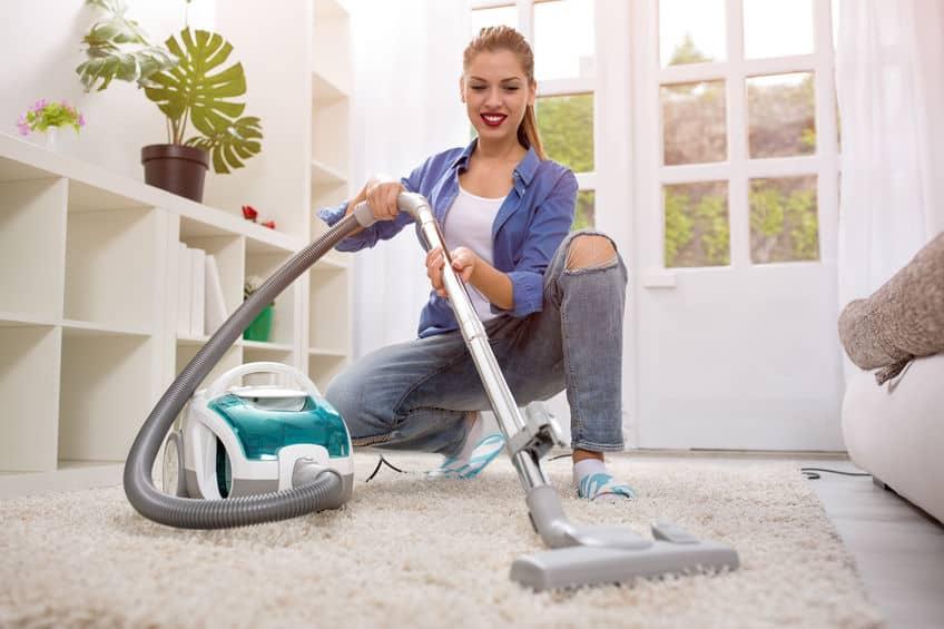 Mulher aspirando o tapete da casa com aspirador de pó sem saco.