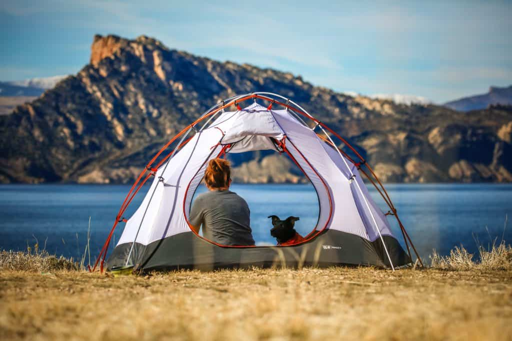 Na foto está uma mulher e um cachorro dentro de uma barraca em um terreno na frente de um lago.