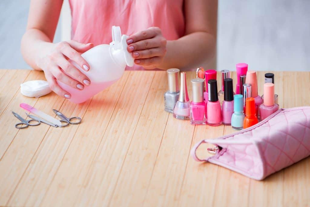 Mulher com algodão na mão mexendo em acetona, há varios esmaltes ao lado.
