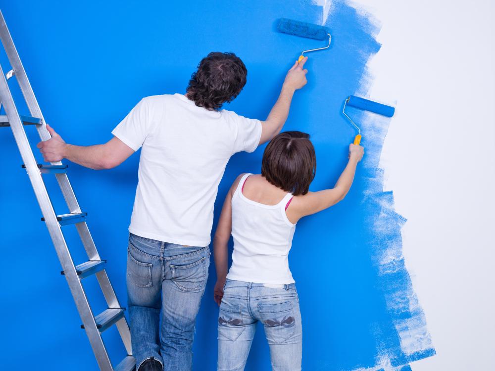 Mulher e homem de costas pintando uma parede de azul. O homem está em cima de uma escada expansível.