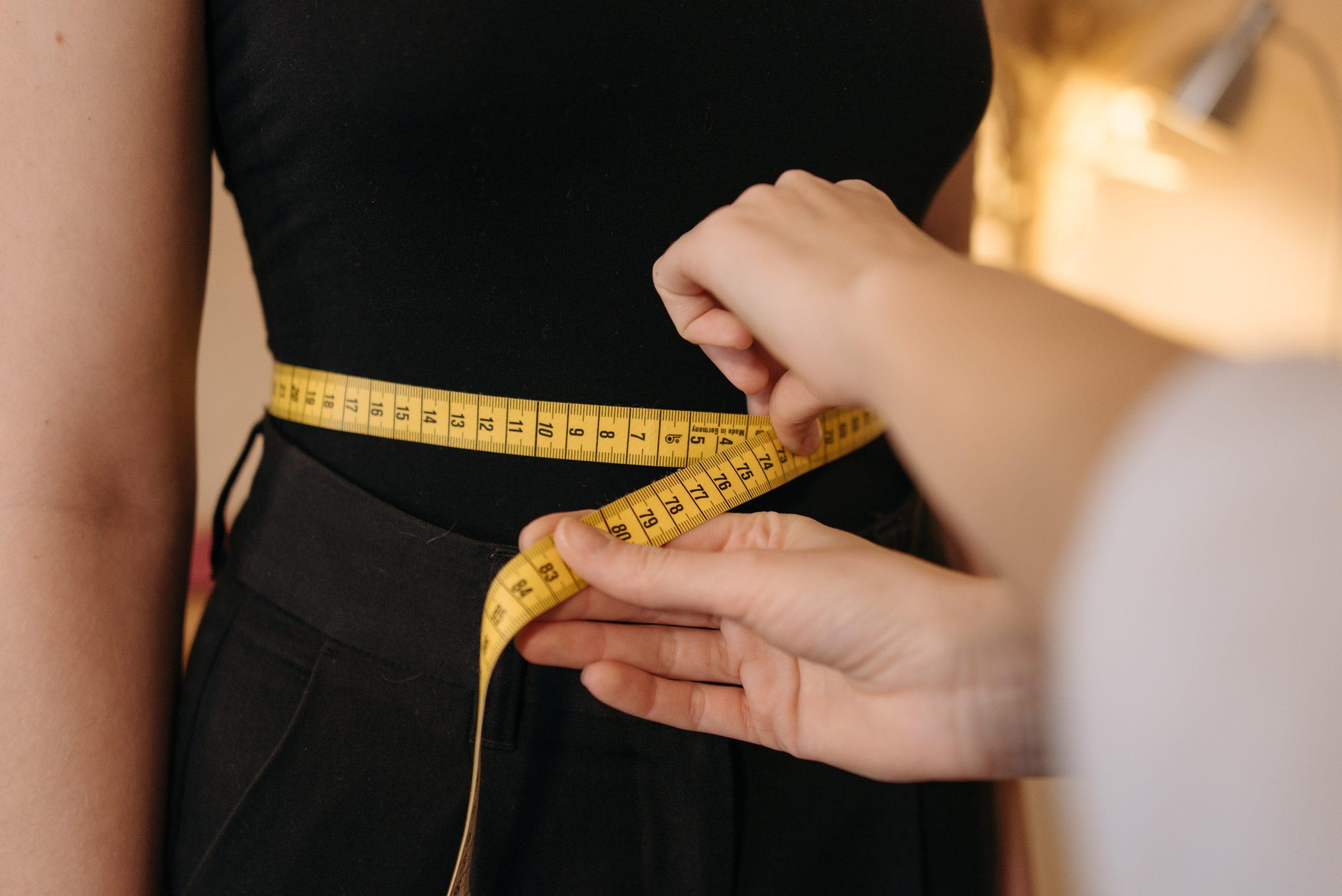 Na foto uma pessoa medindo a cintura de uma mulher com uma fita métrica.