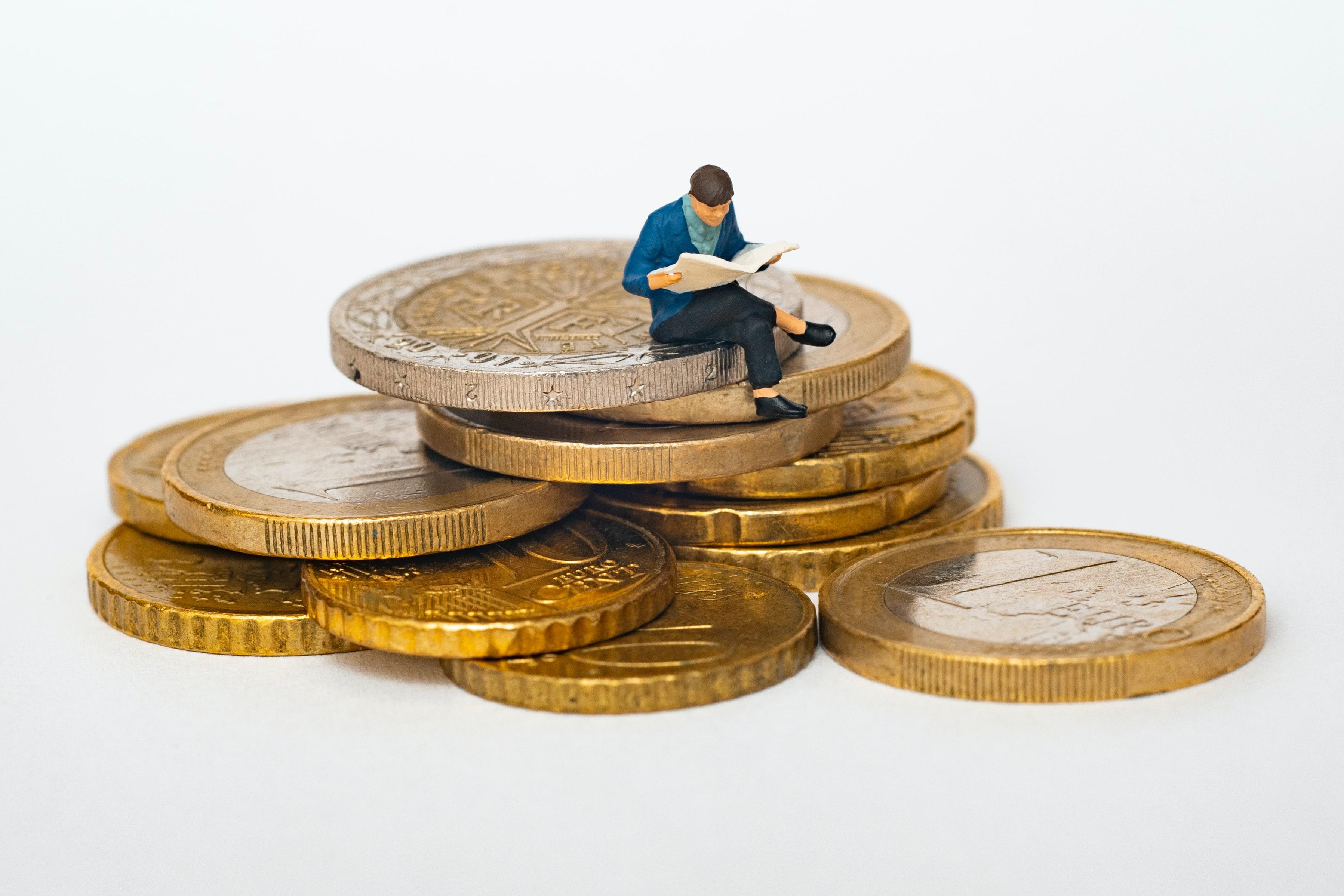 Eine kleine Figur sitzt auf einem Haufen von Münzen und liest die Zeitung. Die Münzen sind im Vergleich zur Figur sehr groß.